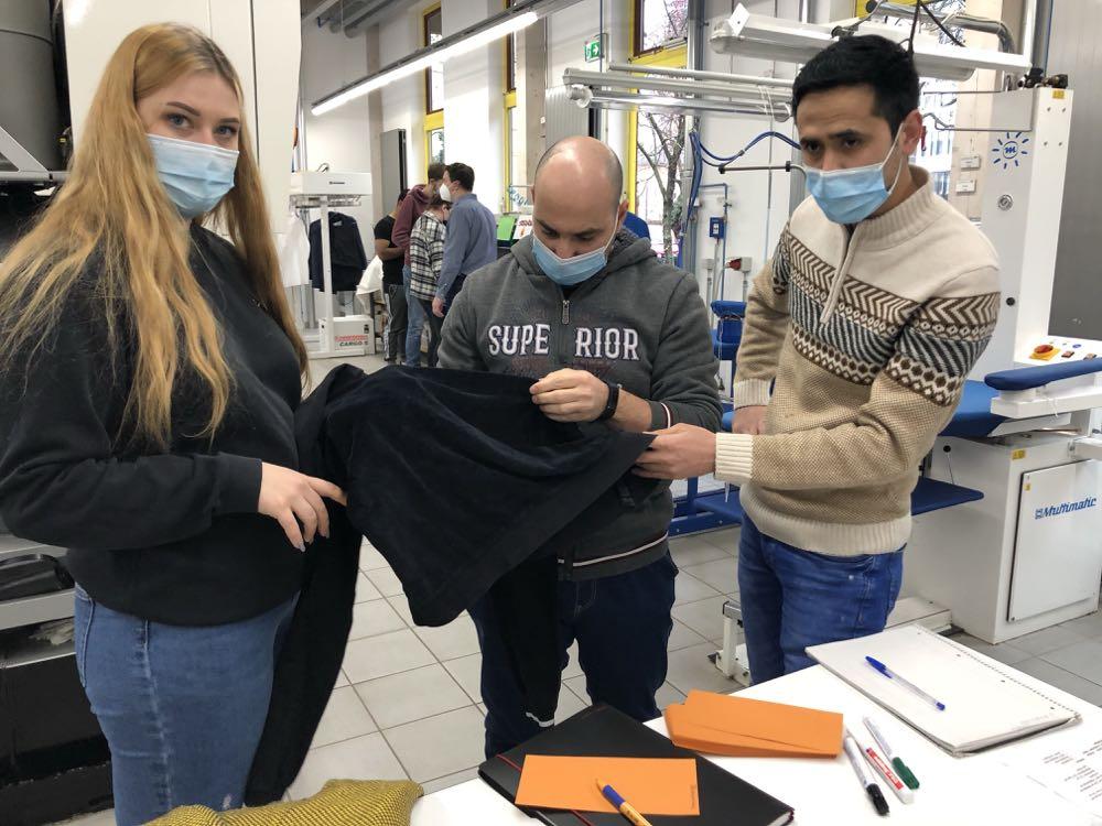 Textilreiniger-Azubis untersuchen Kleidung auf Schäden